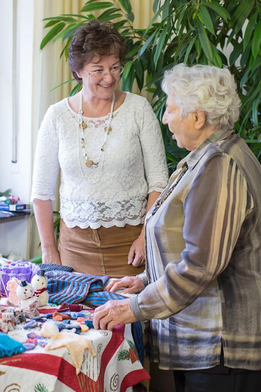 A runde Sach-Projektkoordinatorin Anna-Maria Blau und Frau Seifert Sprecherin Granny Socks vor einem Tisch mit Strickwaren